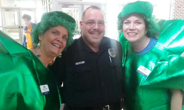 Agent and woman wearing green costumes standing with police officer