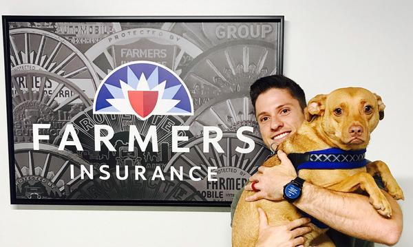 Agent Lukas Perry holding a dog, standing in front of a framed photo of the Farmers logo.