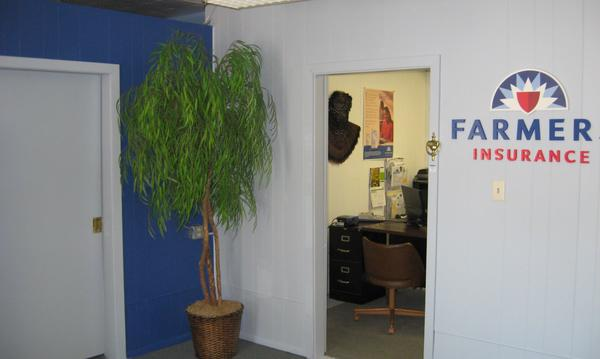 Inside photo of the office with Farmers Insurance logo on white wall and plant to the left of the door.