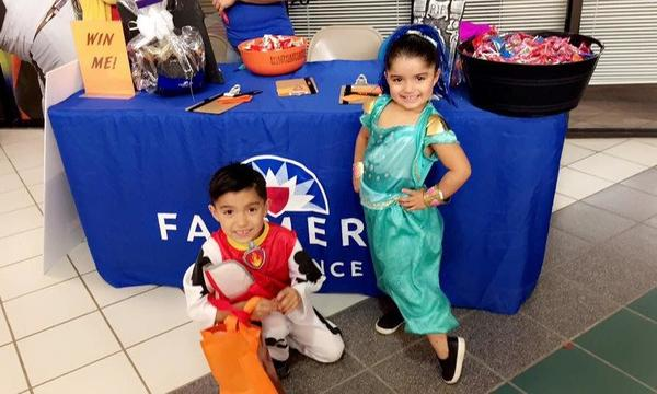 Two children in costume in front of the Ana Jaquez Agency table at Trick-or-Treat 2017.
