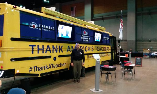 "Agent Michael Matica in front of a Farmers Insurance ""Thank America's Teachers"" promotional bus."