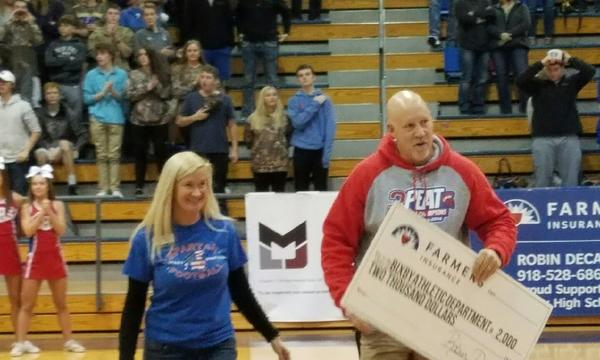 A man and woman presenting a big check at a sporting event.