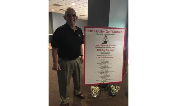 "A man stands in front of a ""2017 Boiler Golf Classic"" poster."