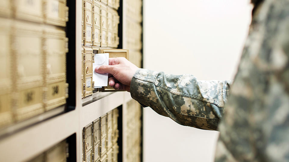 man wearing military uniform getting mail from mailbox