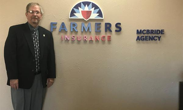 Marty Mcbride Agency male employee standing in the office next to the Farmers logo.