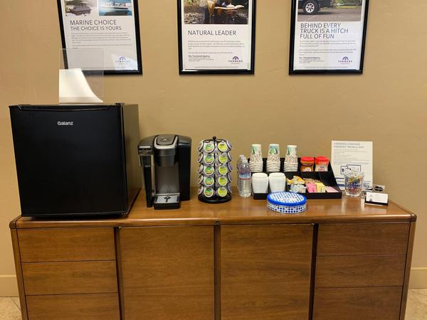 Kitchen counter with coffee products and a fridge