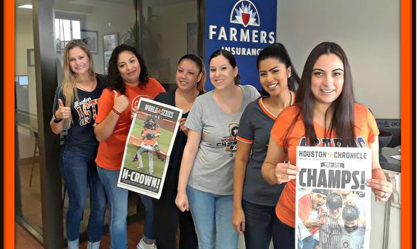Staff members pose with posters for the Houston Astros