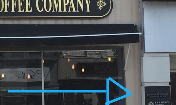 arrow pointing to agency plaque in storefront