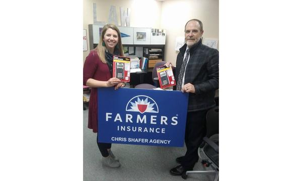 Agent Chris Shafer with a woman holding a Farmers Insurance sign and supplies.
