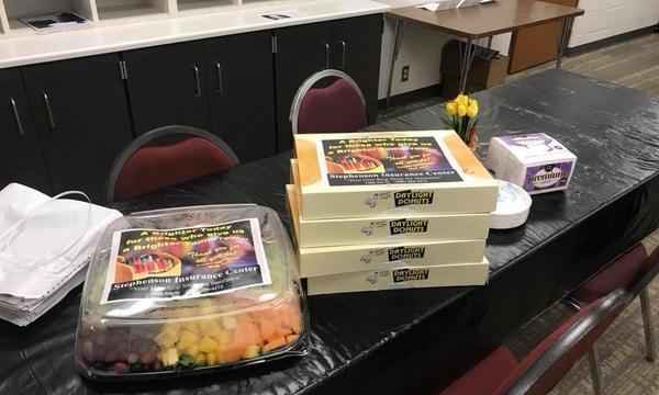 A container of fruit salad and multiple stacked boxes of doughnuts sitting on a table