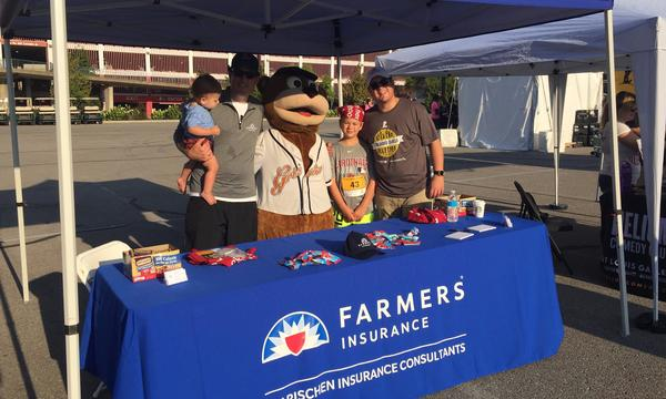 Agent Christopher with a young boy, a bear mascot, another man holding a small child in front of a Farmers booth.