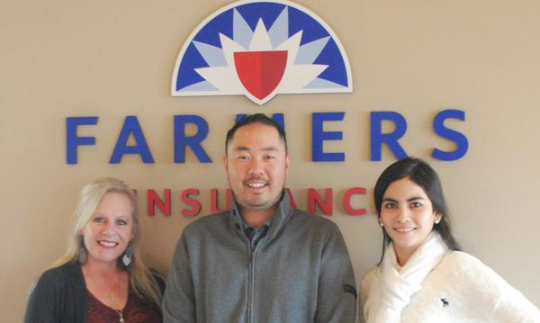 Agent David Kim standing with two staff members in front of the Farmers Insurance logo.