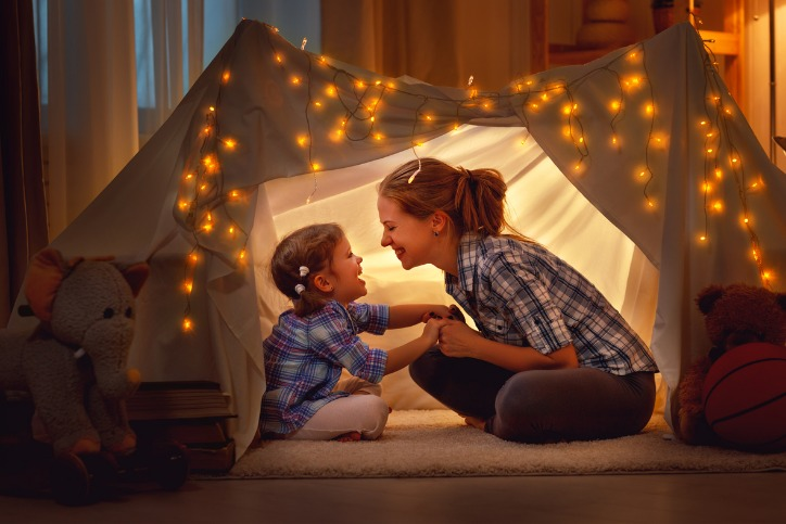 Mother and daughter in a bedroom sitting in a bedsheet tent smiling at one another