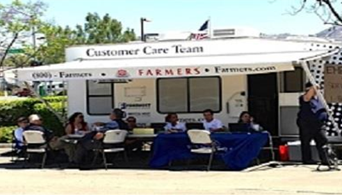 Group sitting in front of a Farmers® trailer