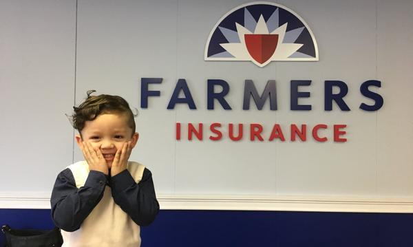 Young boy standing with hands on his face in front of the Farmers Insurance logo