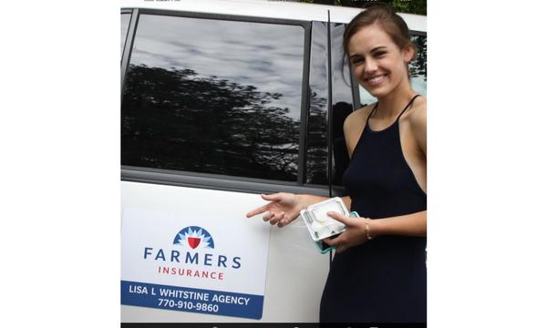 Woman pointing to a Farmers logo on a car