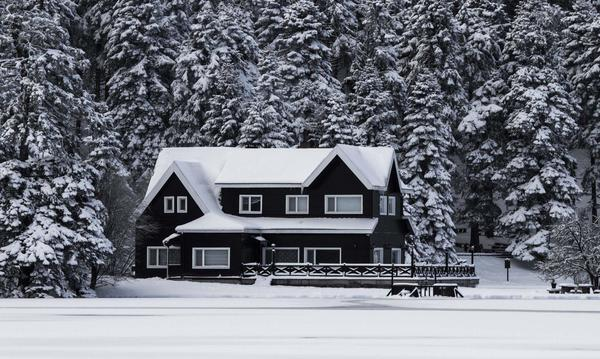 A large house surrounded by trees, covered in a blanket of snow.
