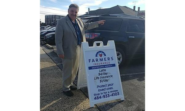 Agent standing in a parking lot pointing while standing next to a sign for the Destefano Agency