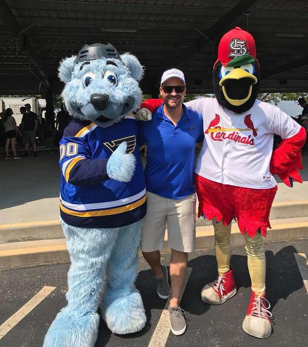 Man standing with two mascots