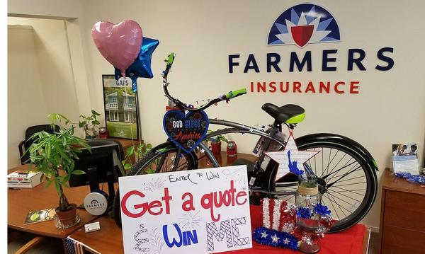 a bike, 2 balloons, a plant, a sign reading Enter to win Get a quote Win me and 4th of July decorations with Farmers logo in the background.