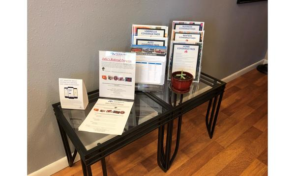 Printed informational handouts on a glass table in the lobby of an office.