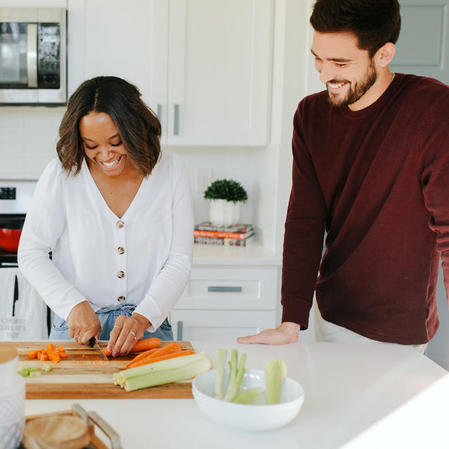 A wife prepares dinner as her husband looks on in their new house thanks to Movement Mortgage.