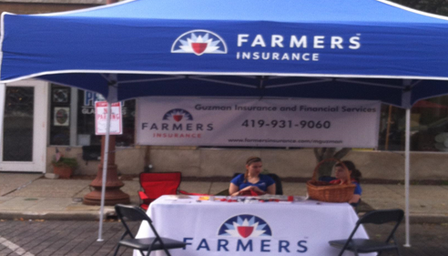 Two people sitting at a Farmers Insurance booth at the local state fair.