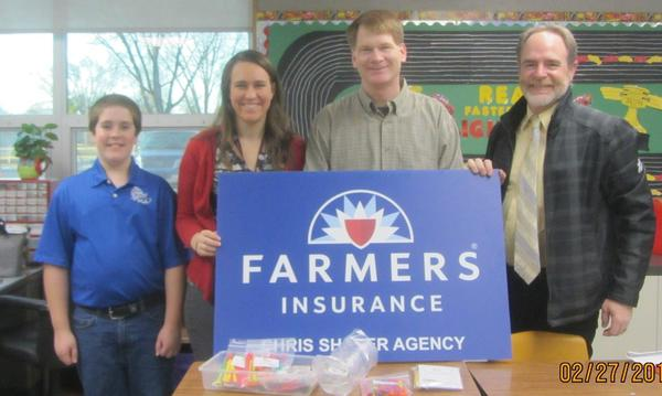 Agent Chris Shafer standing with a man, a woman, and a child holding a Farmers Insurance sign.