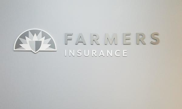 Silver colored Farmers logo on gray wall.