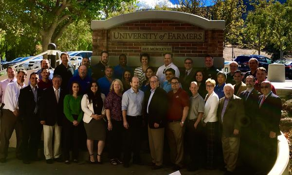 A diverse group of people standing by the Farmers University Sign.