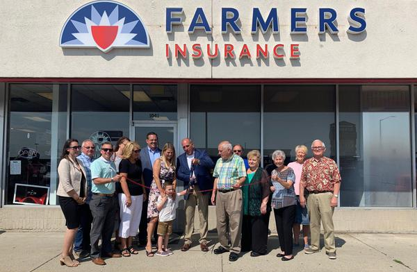 Group of people standing in front of Farmers Insurance storefront