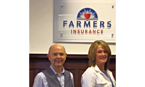 Agent and staff standing in front of the Farmers Insurance logo