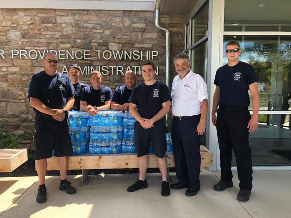 Group of men standing with cases of bottled water