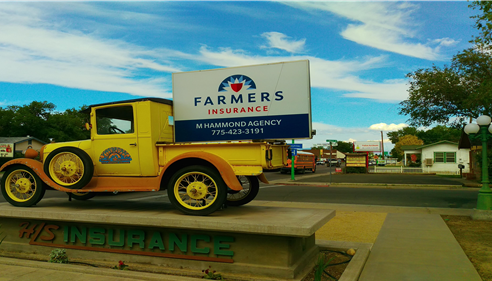 A sign for The Hammond Agency in the flatbed of old-time truck.