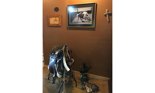 A saddle rack in the corner of an office with a photo of a bull rider on the wall