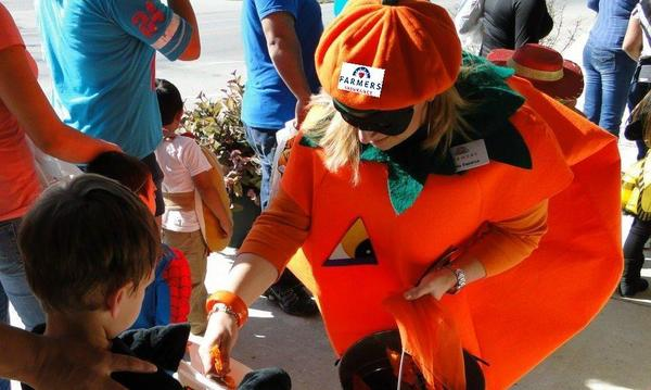 A lady in a pumpkin suit handing out candy