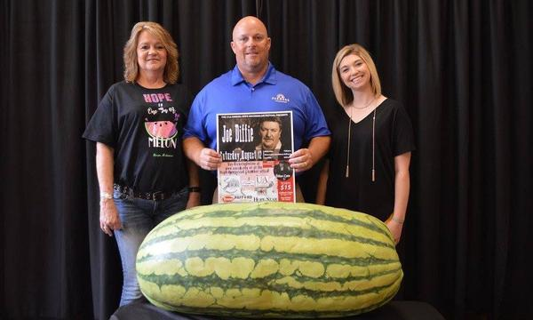 Agent Jamee and two females next to a very large watermelon.