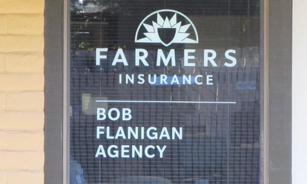 Photo of Farmers Insurance logo on Agency's door.