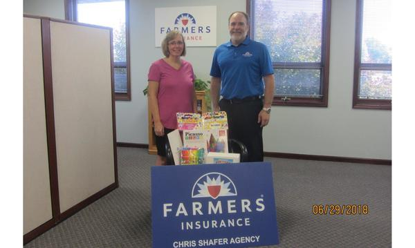 Agent standing with woman in front of Farmers sign