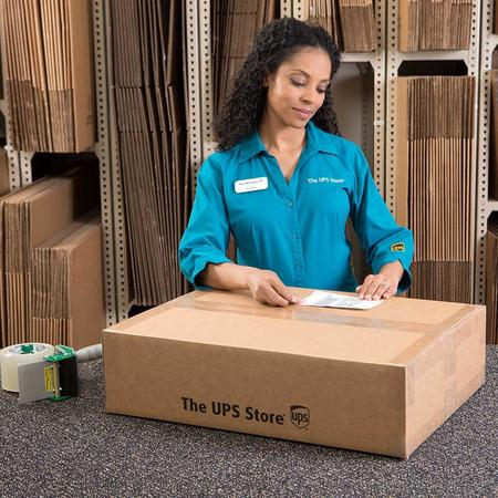 Female The UPS Store clerk placing shipping label on package