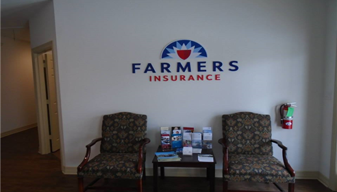 two chairs by a wall with Farmers logo
