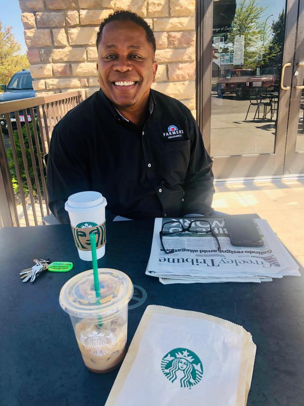 A photo of Farmers Agent, Ronald Williams, enjoying a Starbucks coffee on a sunny day.