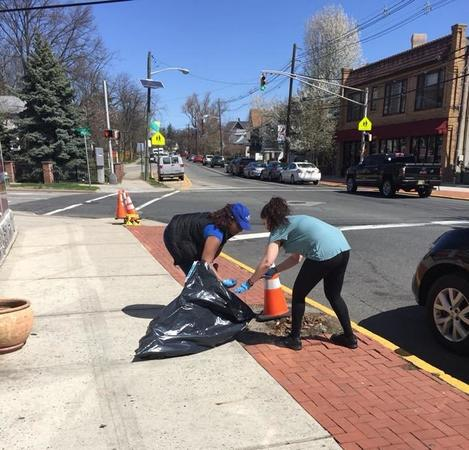 2 people cleaning up the street