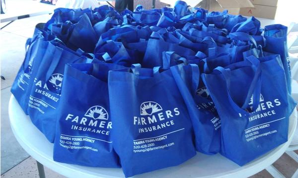 A table full of blue Farmers Insurance branded tote bags
