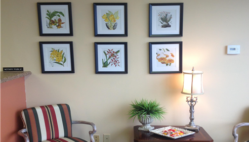 A wall in the agents office with pictures of flowers