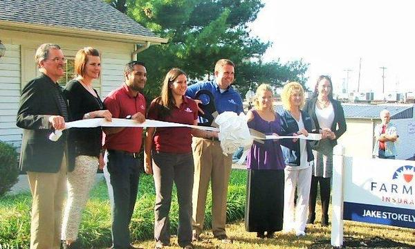 Agent standing with group cutting a ribbon