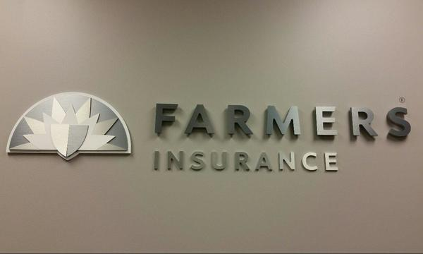 The official Farmers Insurance logo mounted on a wall.