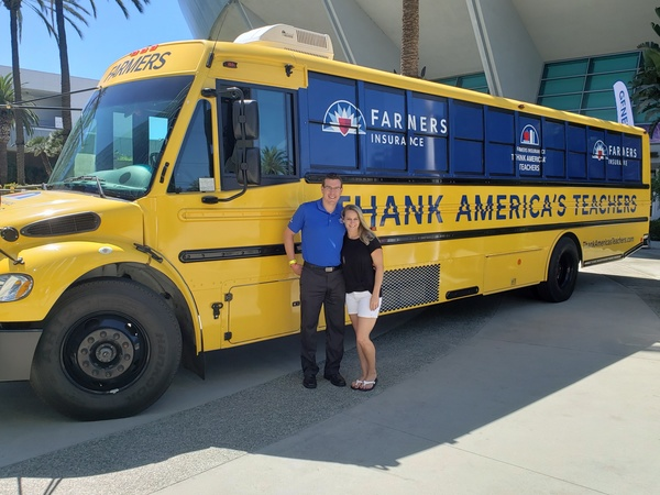 Kyle and Kristen in front of a bus with the Farmers logo on it