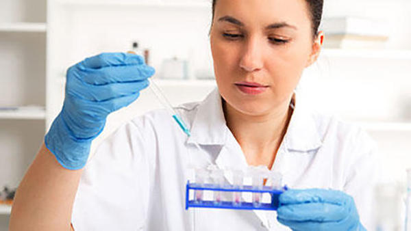 Pharmacist measuring medicines in sample tubes.