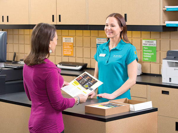 customer and clerk at counter reviewing printed material